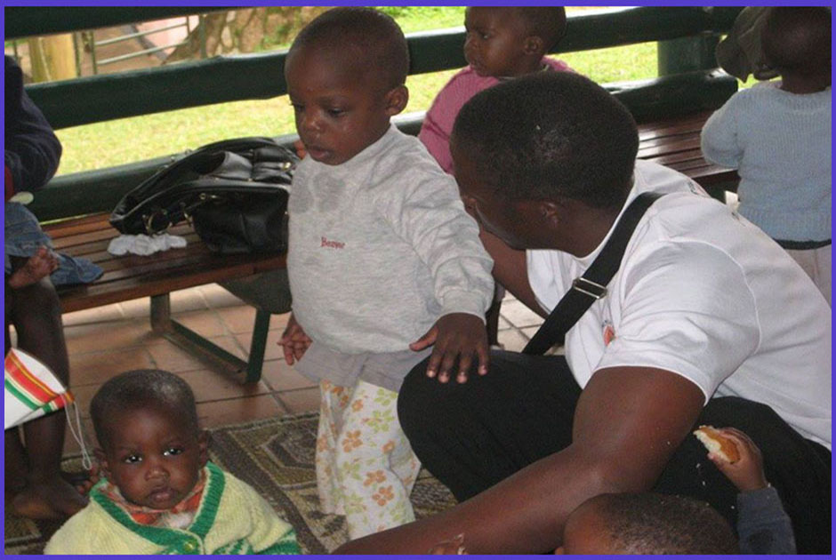 The Managing Director of Volunteers for Change Uganda (V.O.C.U), Geoffrey Kaweesa attending to the babies at Sanyu Babies' Home, when he visited their premises.